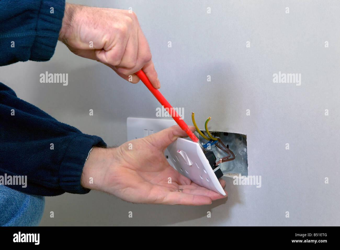 The hands of an electrician installing a power socket Stock Photo