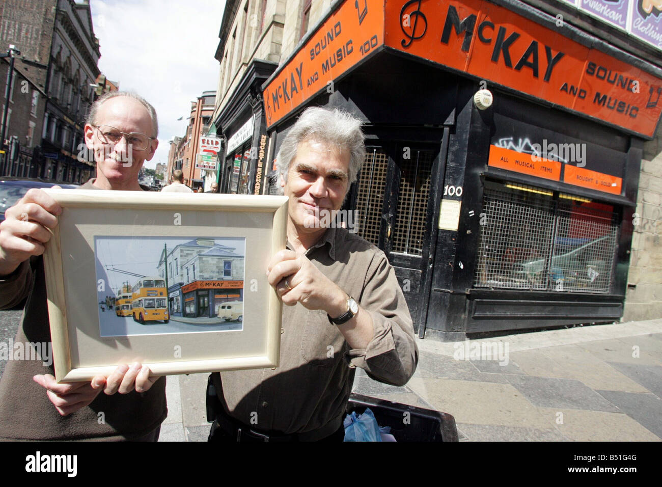 Lindisfarne band member Ray Jackson right presents a painting called Wired for Sound of MaKay sound and music shop - Stock Image