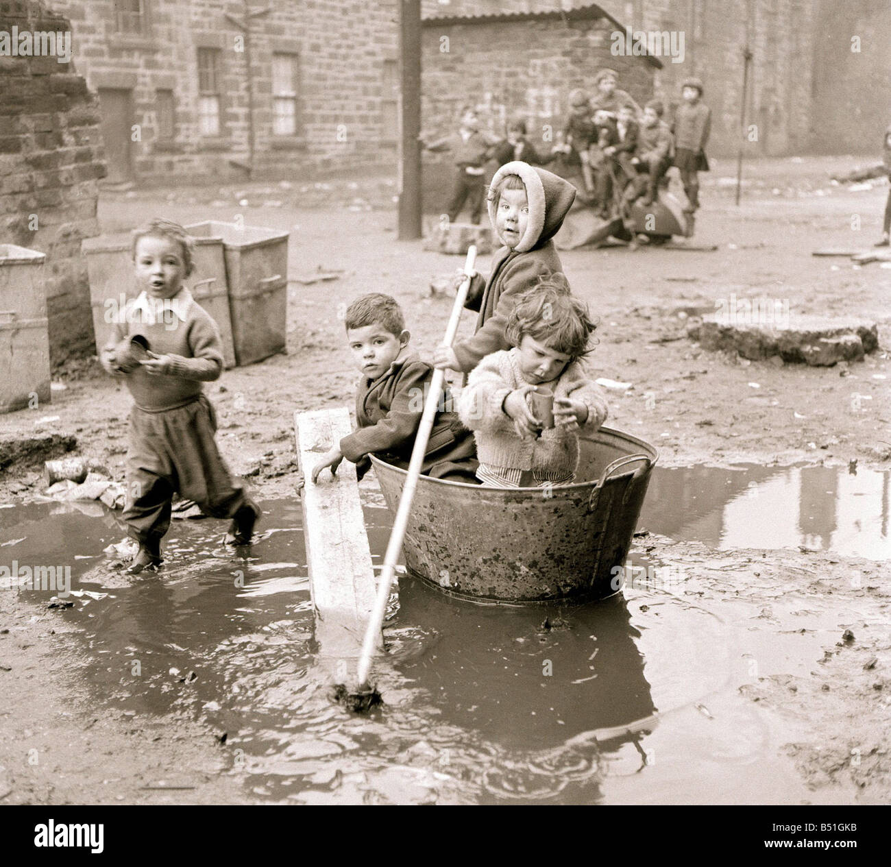 Housing slums in the Gorbals district of Glasgow where children use any materials to hand an old bath tub for a Stock Photo