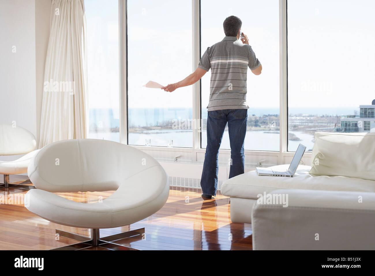 Man with Cellular Phone in Condominium Stock Photo