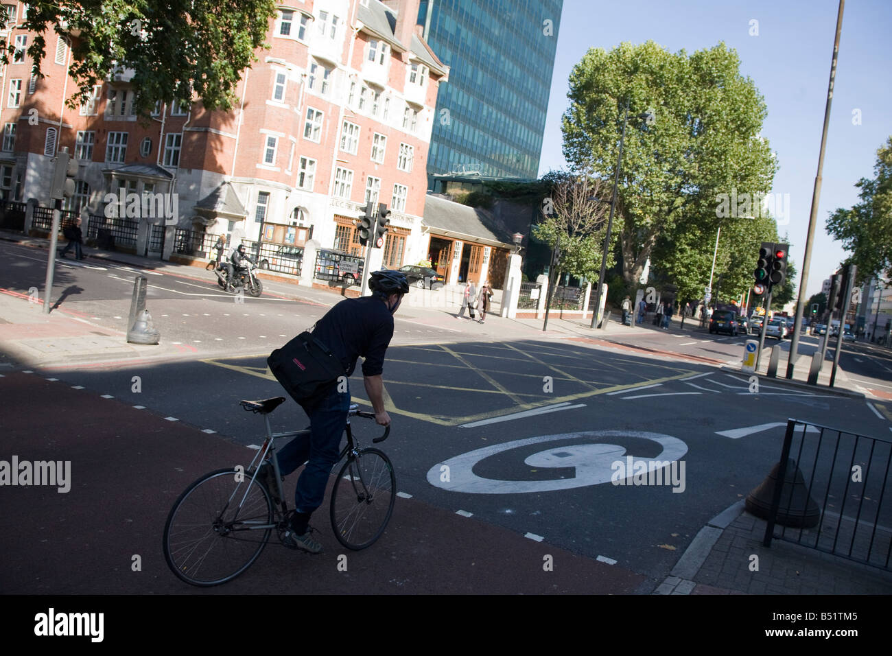 a cyclist turning right on the Euston Road in London to enter the congestion charging zone - Stock Image