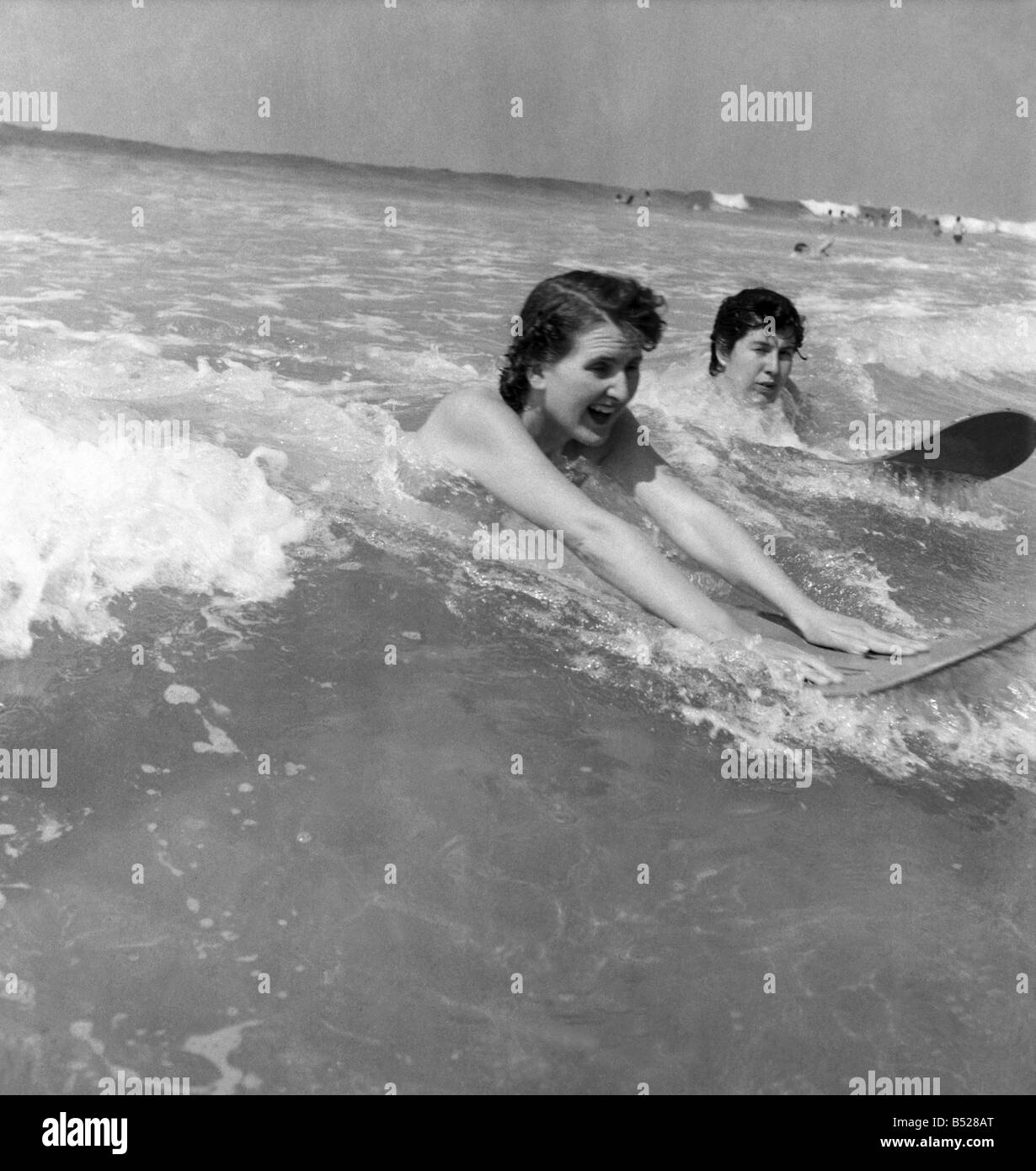 Holidays. Two shop assistants surfing at newquay, Cornwall. May 1953 D2386 Stock Photo