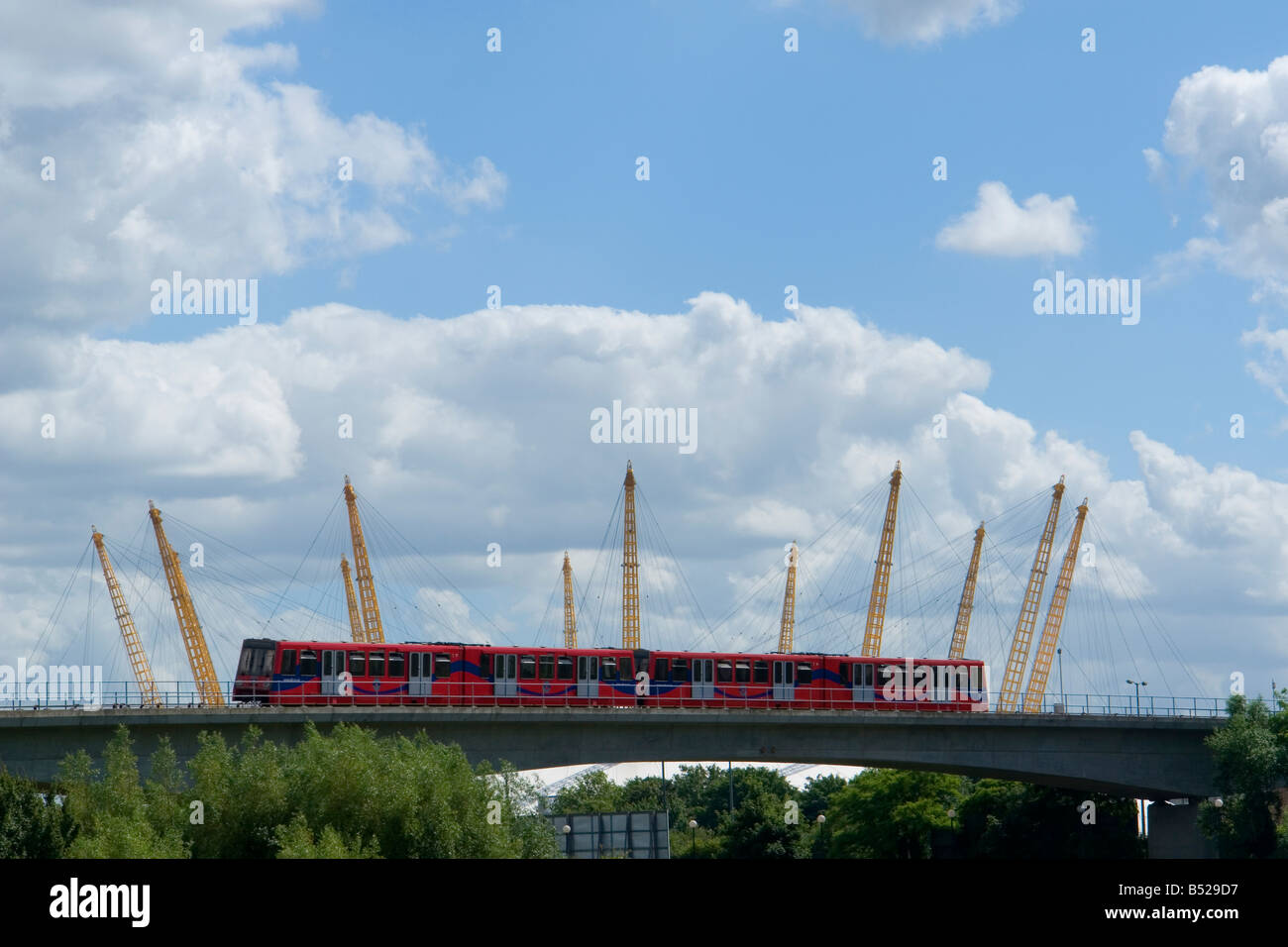 DLR - Docklands Light Railway train with poles of the millenium dome in the background - Blackwall - east London - Stock Image