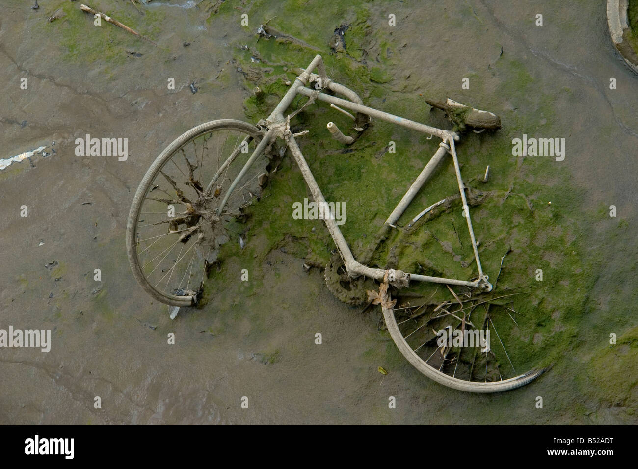 abandoned bike in the mud on the bank of the low tide river Thames in Blackwall - London UK - Stock Image