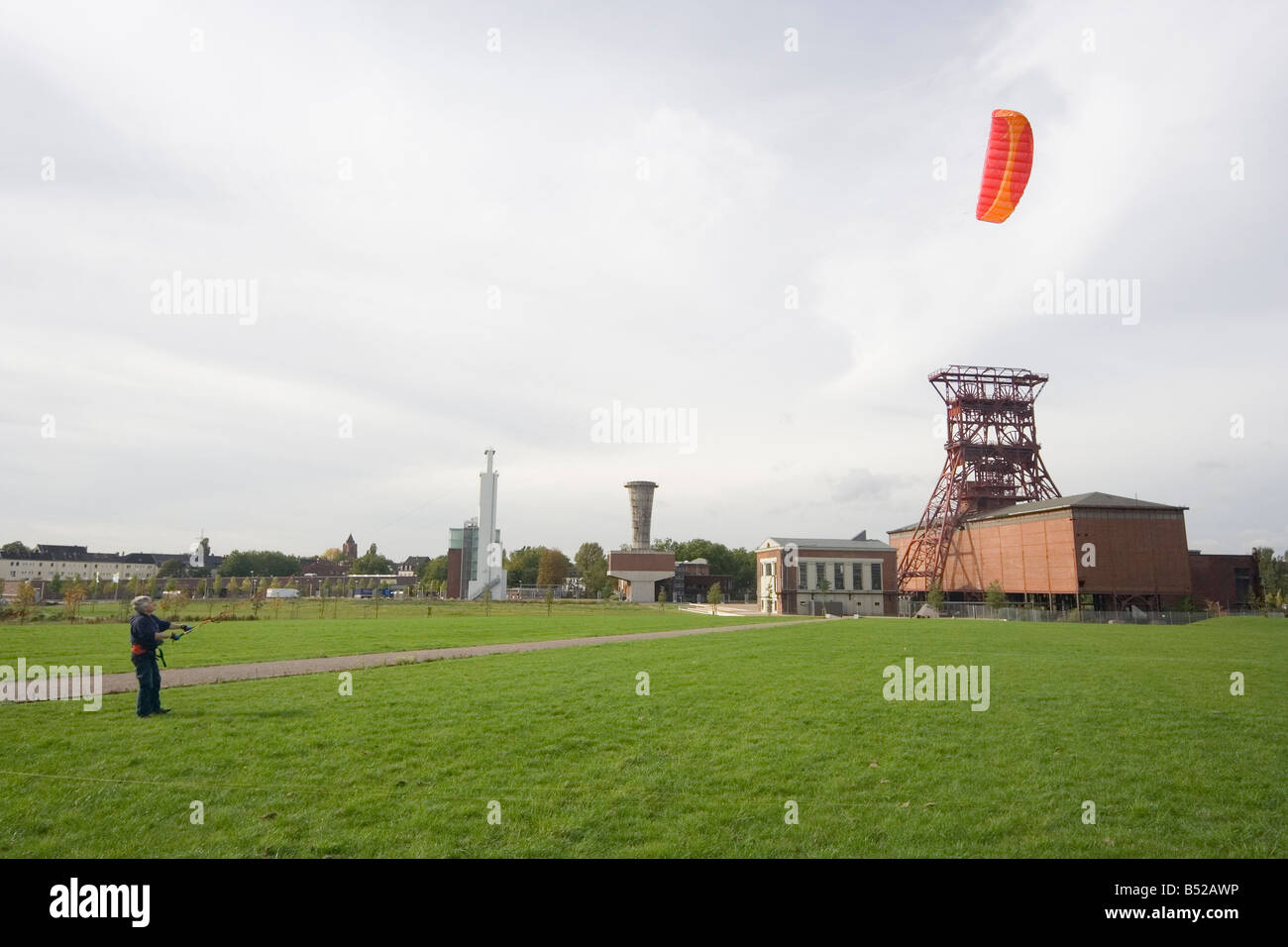 man with a power kite - action in an old industrial area with a shaft tower - Stock Image
