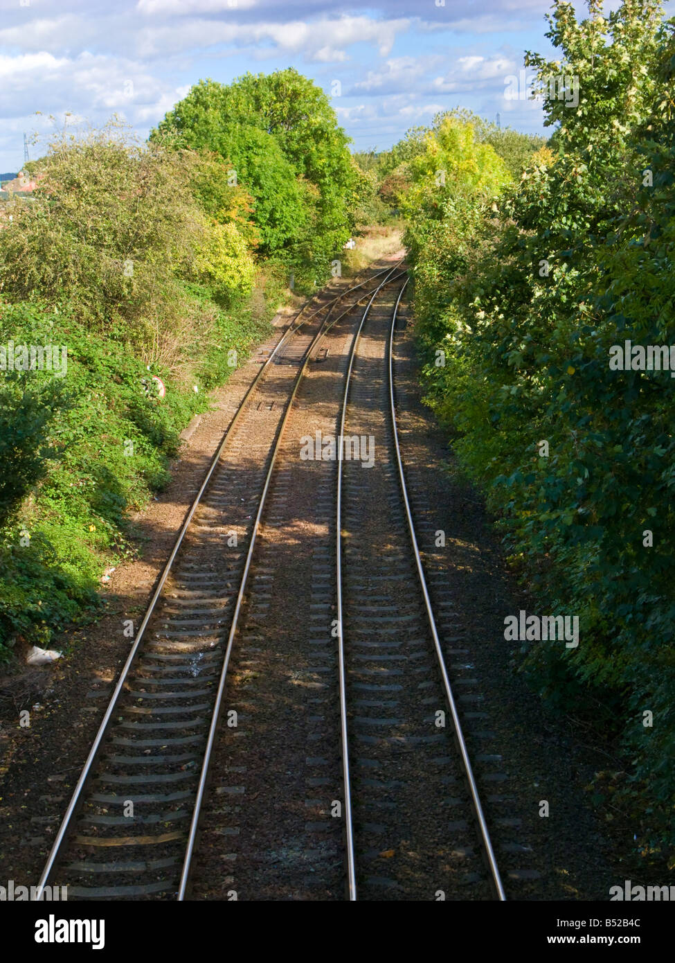 Looking down to railway tracks and leafy cutting in rural England, UK - Stock Image