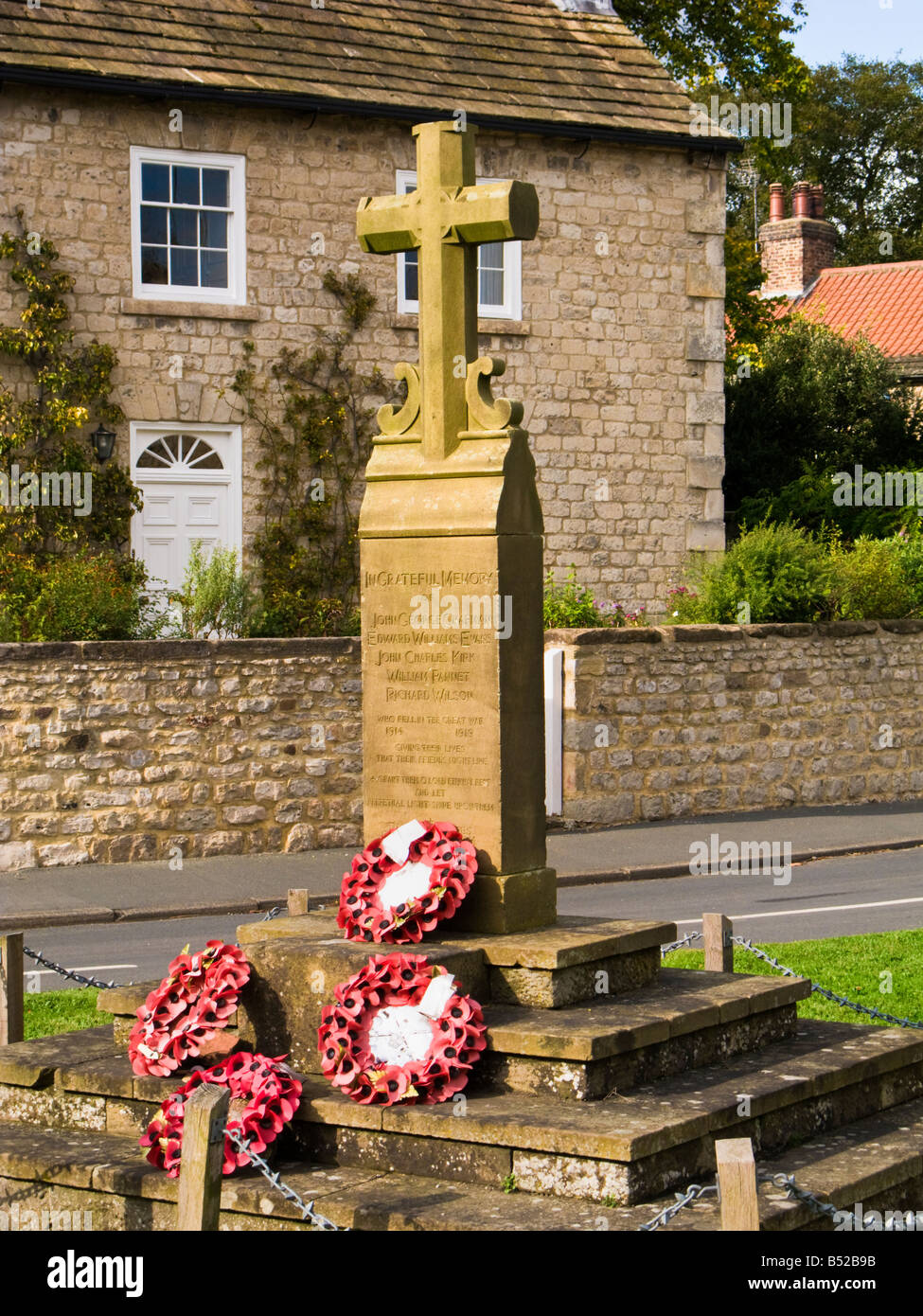 The village war memorial and poppy wreaths at Goldsborough, North Yorkshire, England, UK - Stock Image