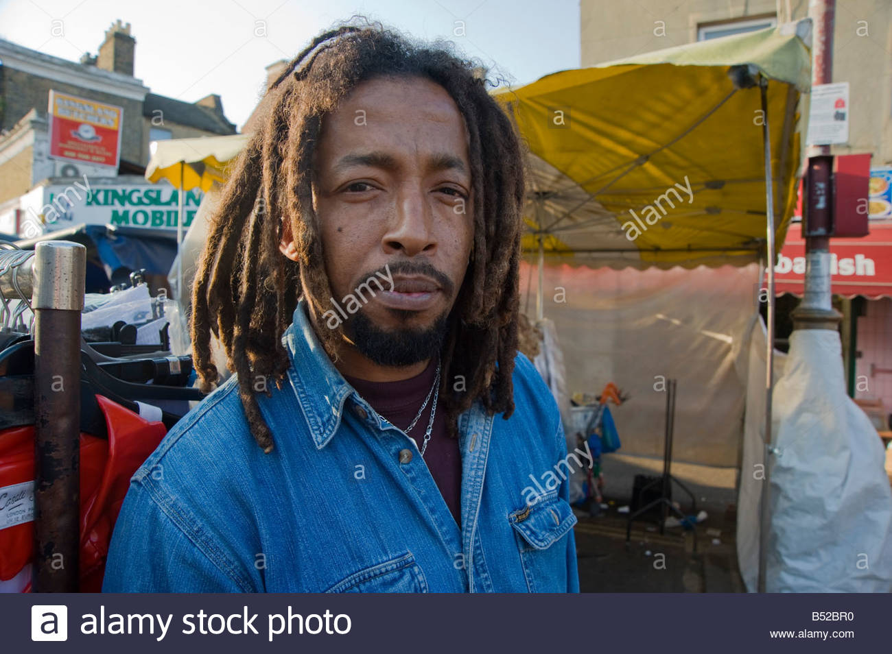 A Senegalese rasta man with dreadlocks looks into the camera at Ridley road market Dalston Hackney East London - Stock Image
