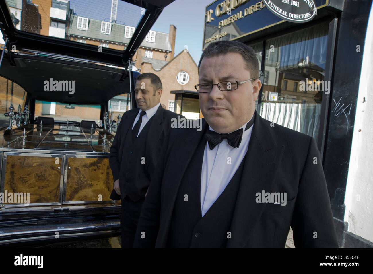 Two Undertakers waiting for a coffin, beside their hearse Hackney, Dalston, East London - Stock Image