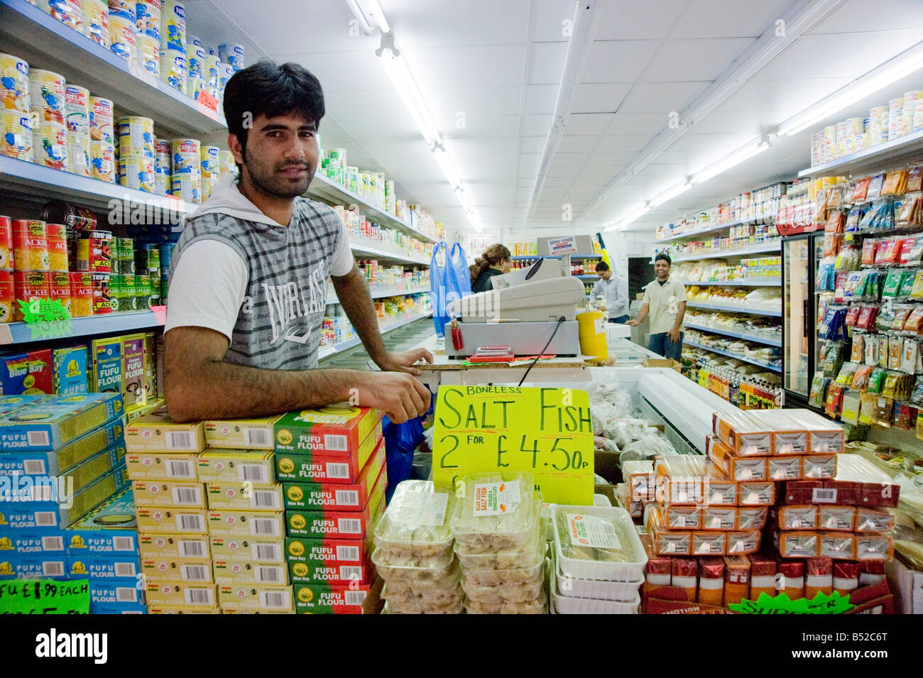Indian shopkeeper looking into camera Dalston Hackney East London UK - Stock Image