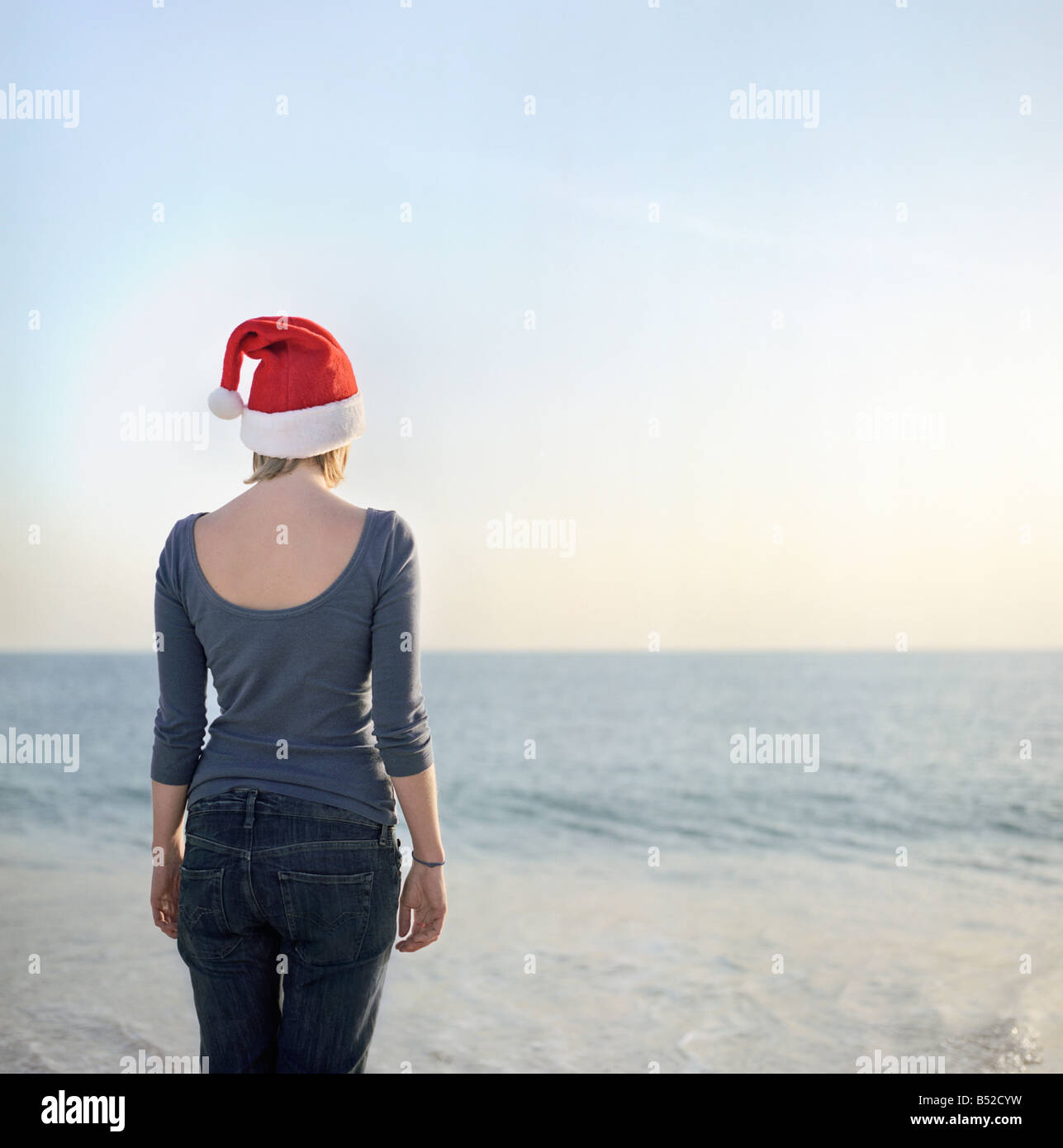 09bd1fecd3f Rear view of a young woman wearing a Santa hat and standing at the coast  Portugal