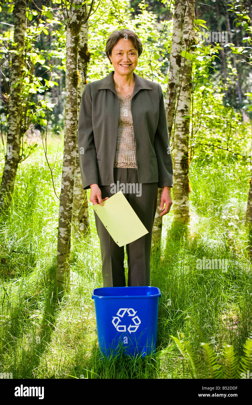 A mature Asian businesswoman standing in a green forest dropping a piece of paper into a recycle bin - Stock Image