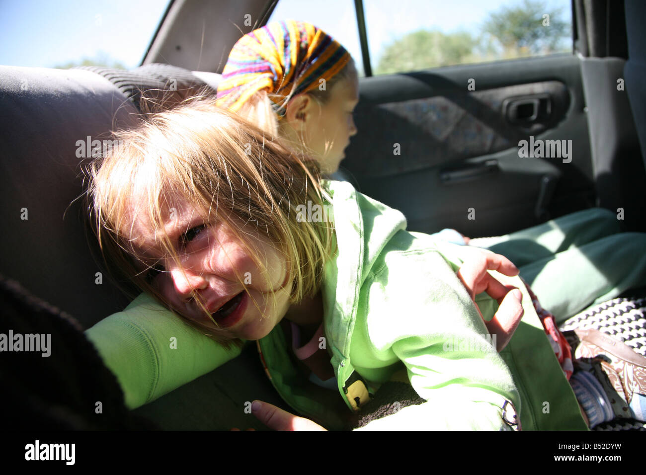 Three year old girl crying with her older sister in backseat of car Teary eyed girl sad distraught Siblings Younger - Stock Image
