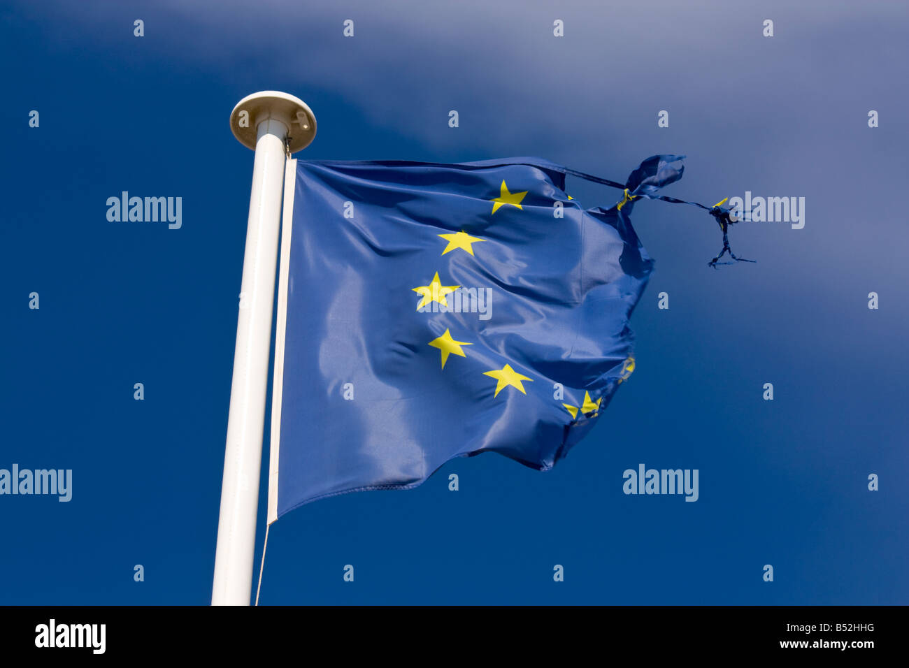 A tattered flag of the European Union waves in the wind - Stock Image