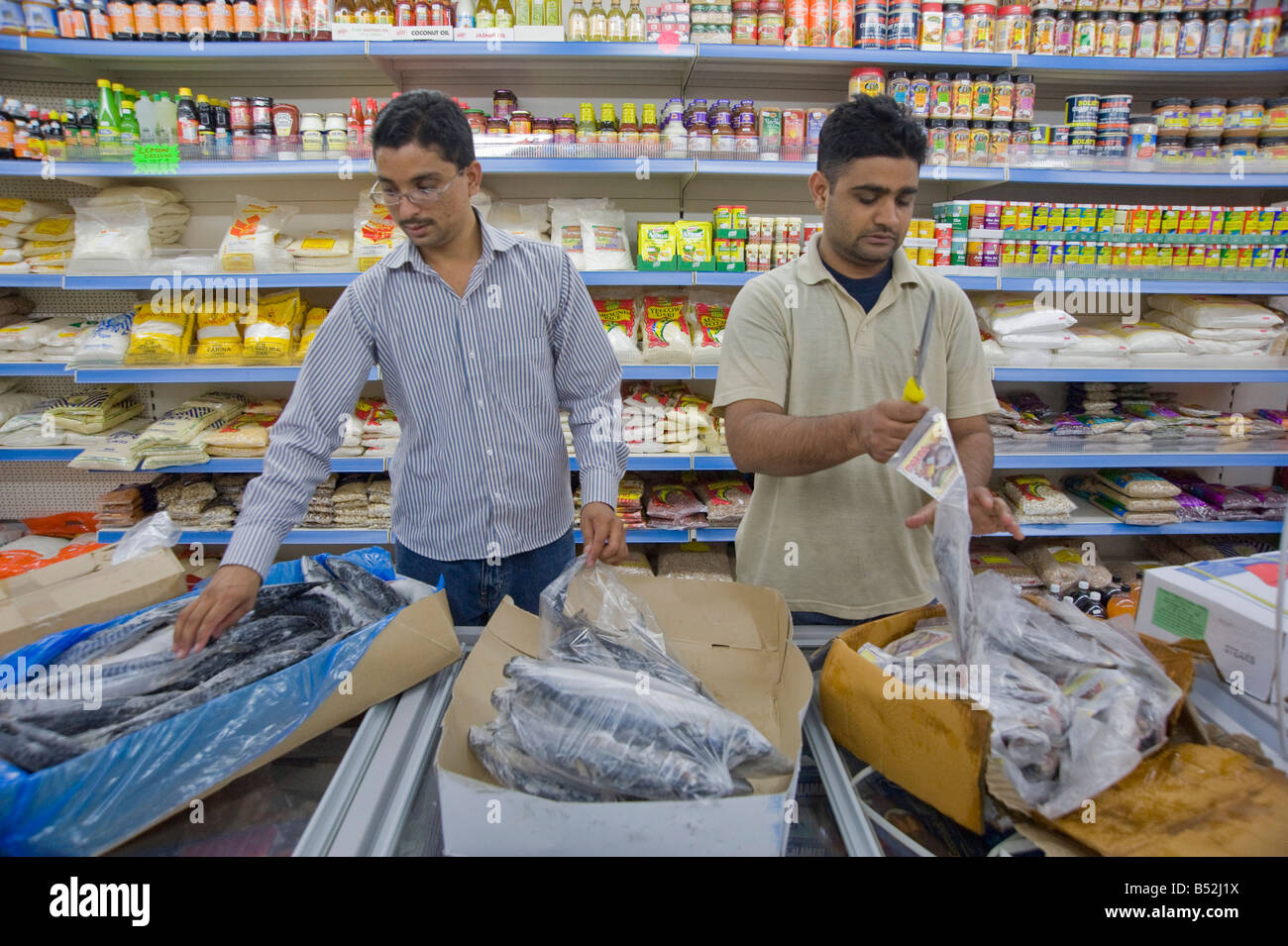 Indian Workers sorting frozen fish in a shop in Dalston Hackney East London UK - Stock Image