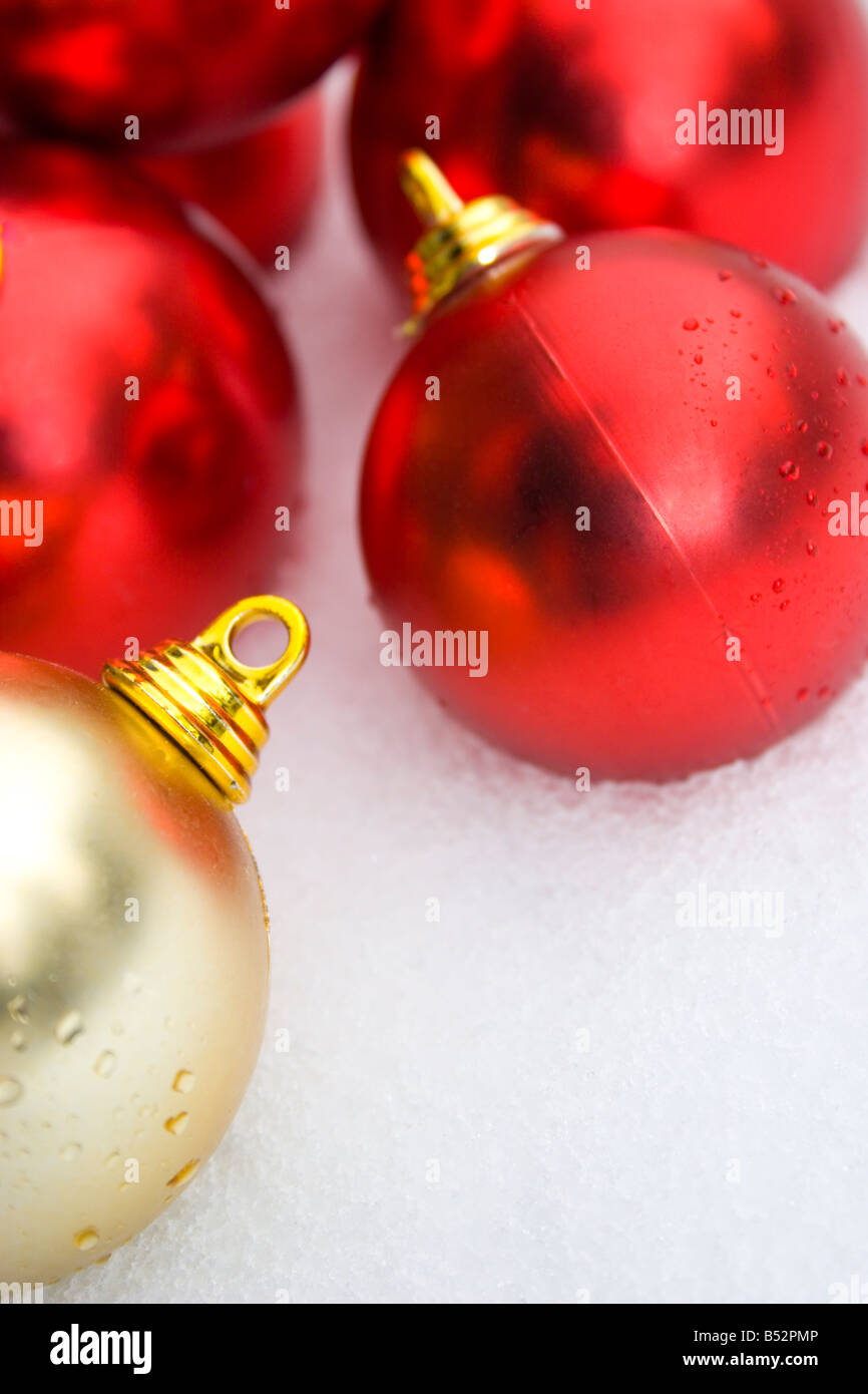 red and gold christmas tree decorations in the snow - Stock Image