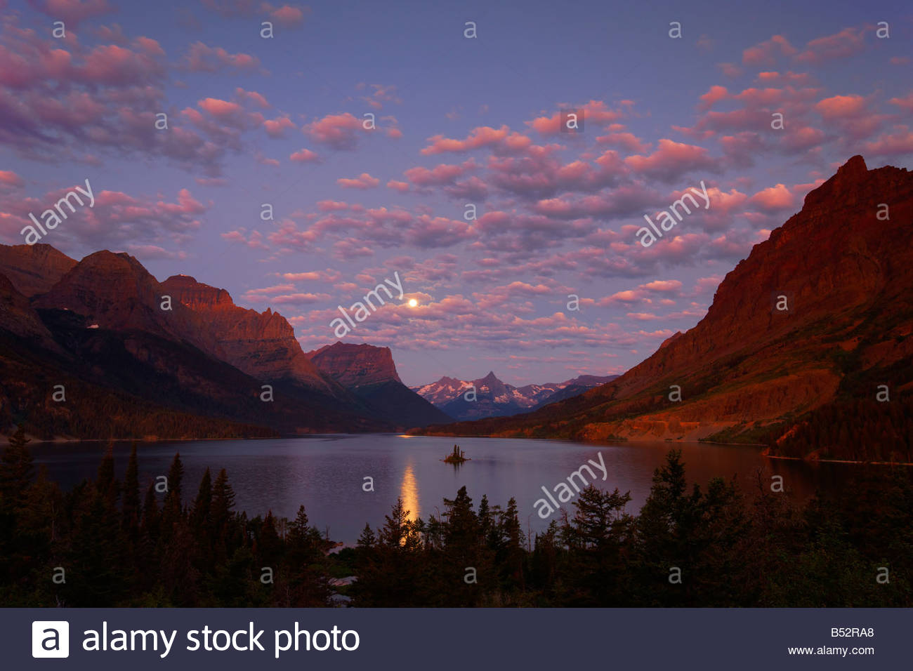 The full moon sets over St. Mary Lake as the first light of day reddens the skies over Glacier National Park, Montana. - Stock Image