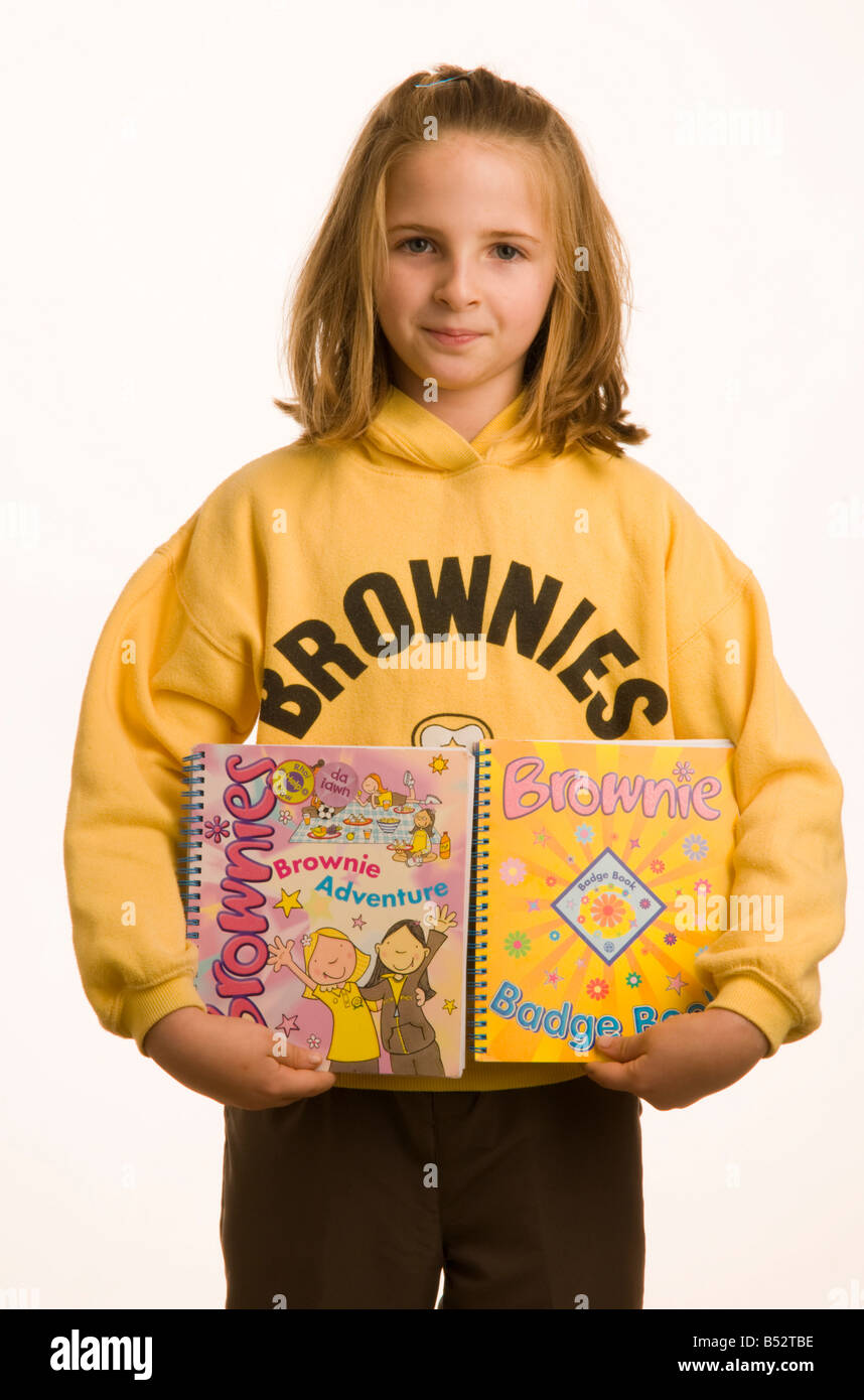 10 year old girl dressed in Brownies uniform holding books - Stock Image