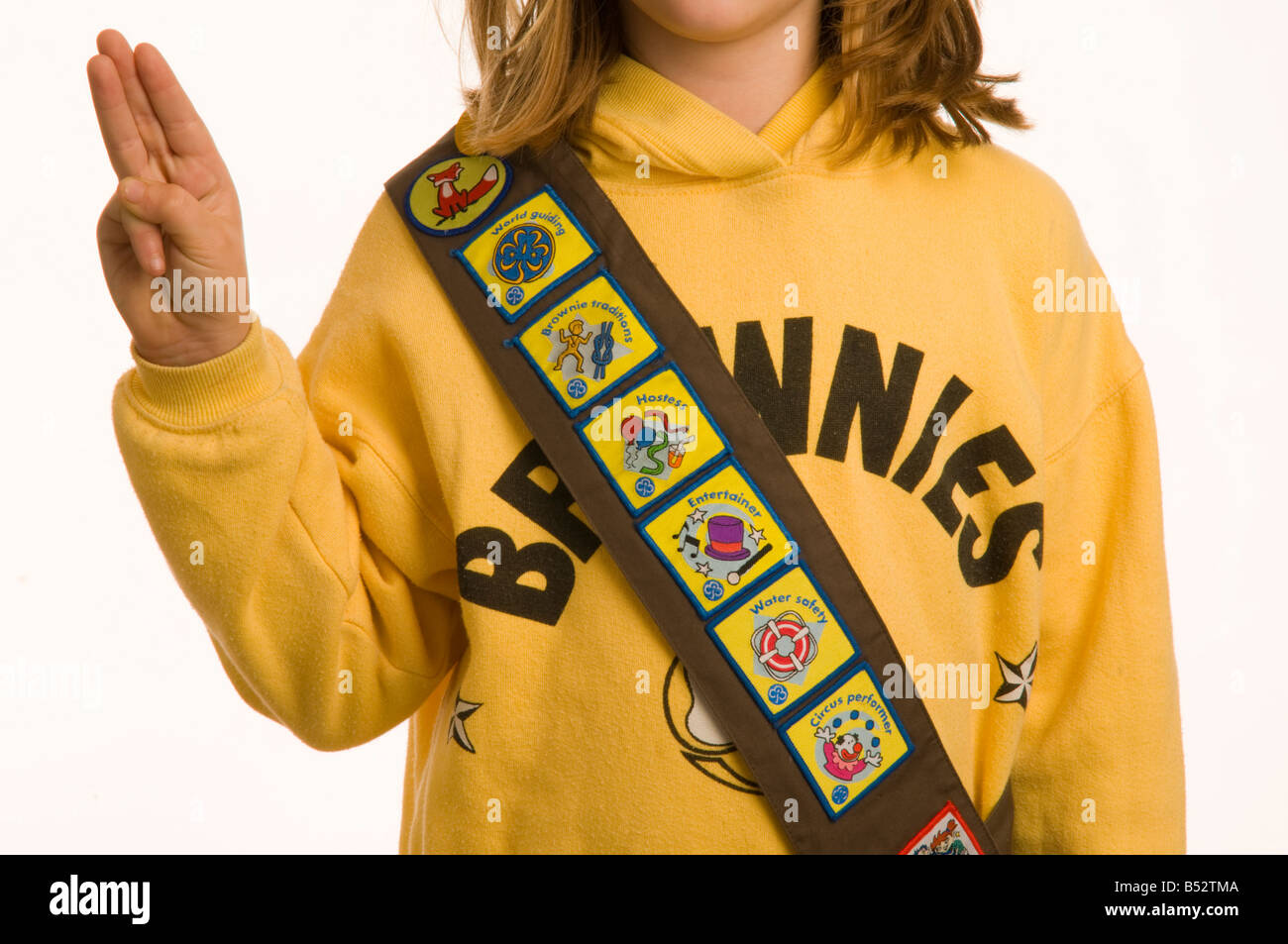 10 year old girl dressed in Brownies uniform showing her collection of merit badges for completing tasks and acquiring - Stock Image