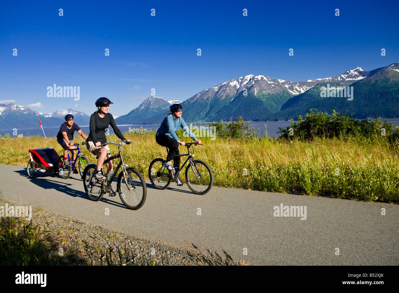 Group of bikers with baby in storller on the Bird Point to Girdwood bike trail along Turnagain Arm, Southcentral - Stock Image