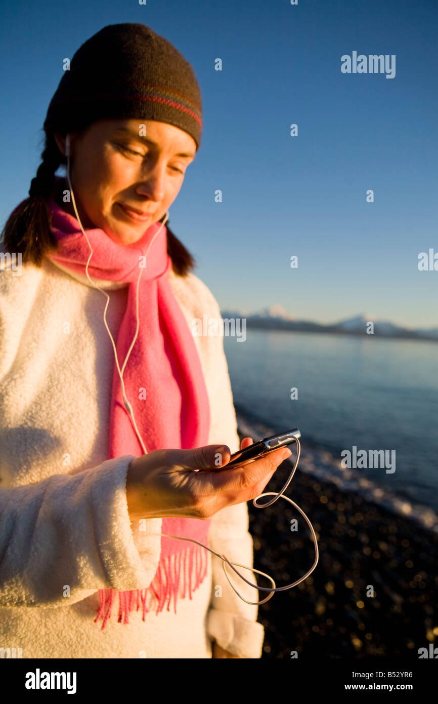 Woman listens to iPod at Bishops Beach at Kachemak Bay in Homer, Alaska - Stock Image