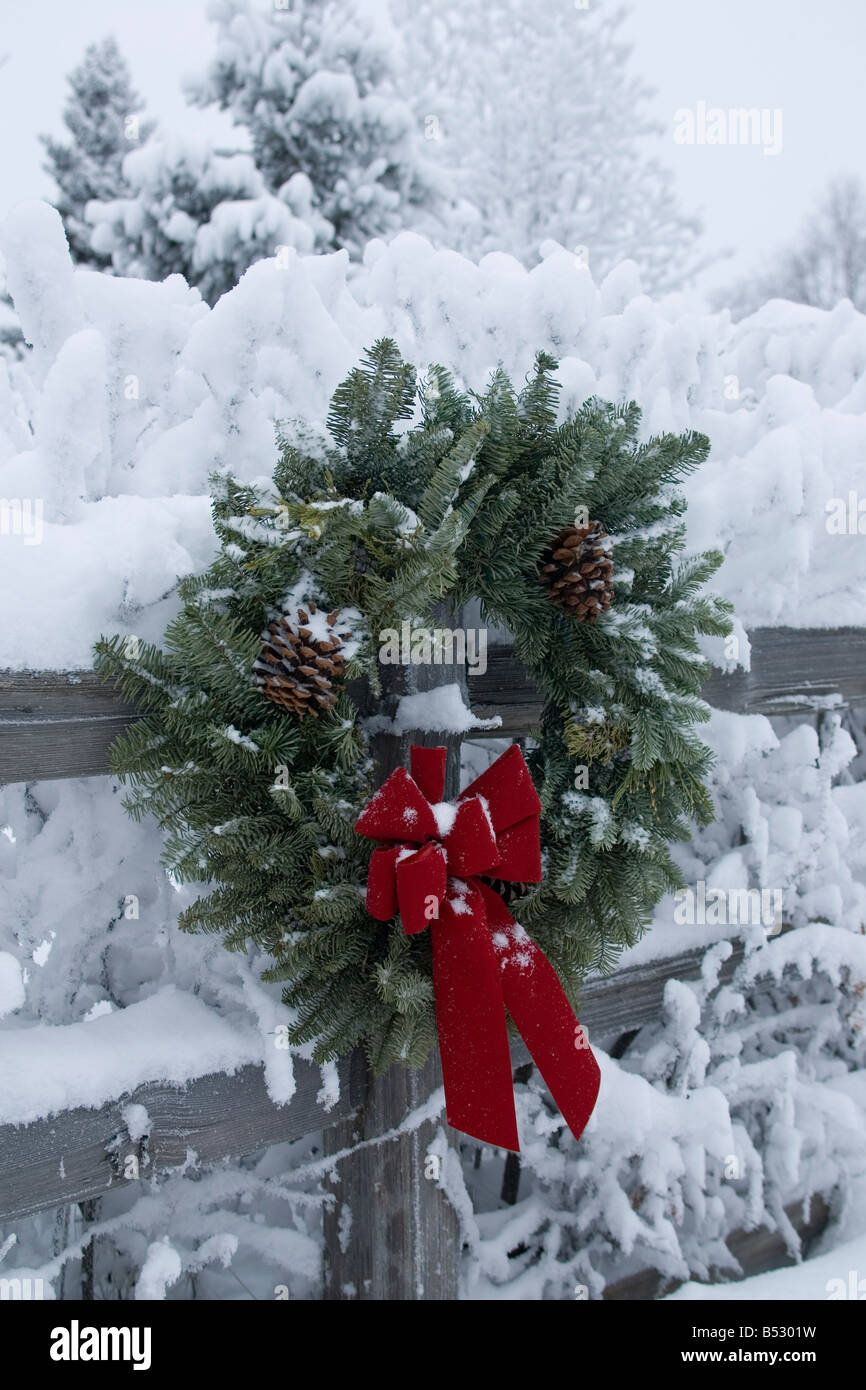 Holiday christmas wreath hanging on snow covered split rail fence Anchorage Alaska Southcentral Winter Stock Photo