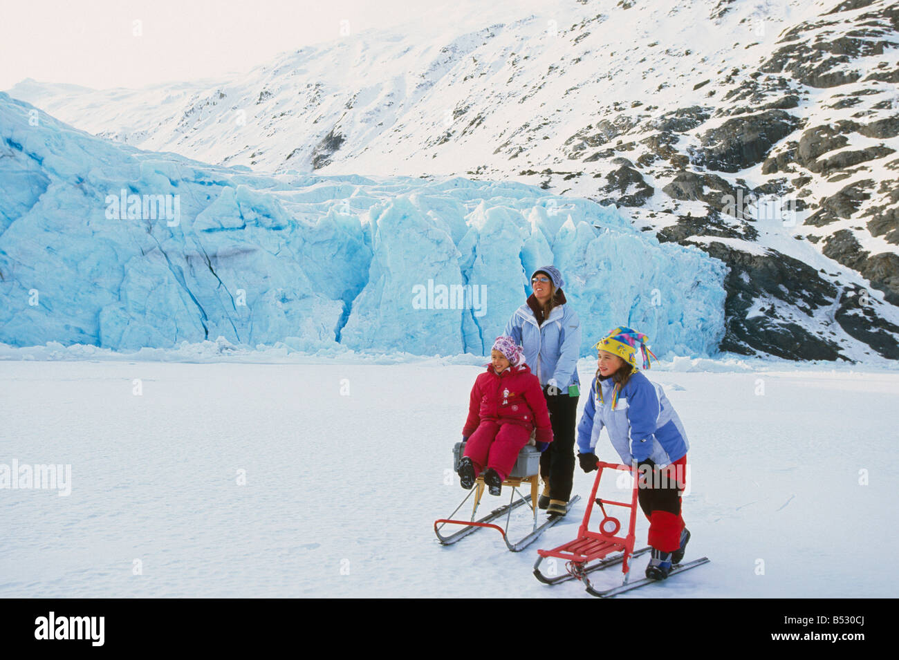 Family kick sledding together on Portage Lake Southcentral Alaska Winter Portage Valley - Stock Image