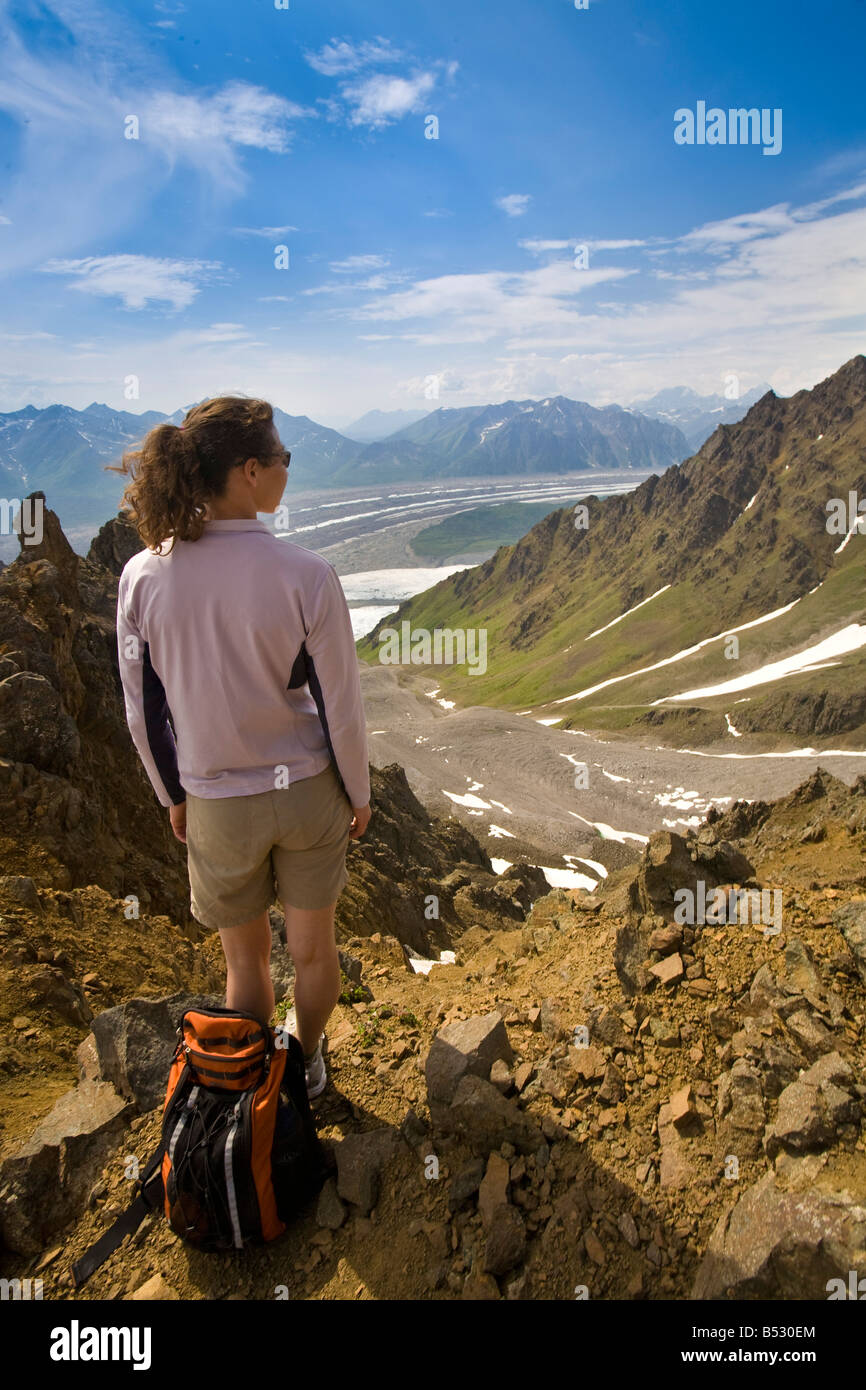 Woman standing on ridge overlooking the Root and Kennicott glaciers in Wrangell-St. Elias National Park, Alaska - Stock Image