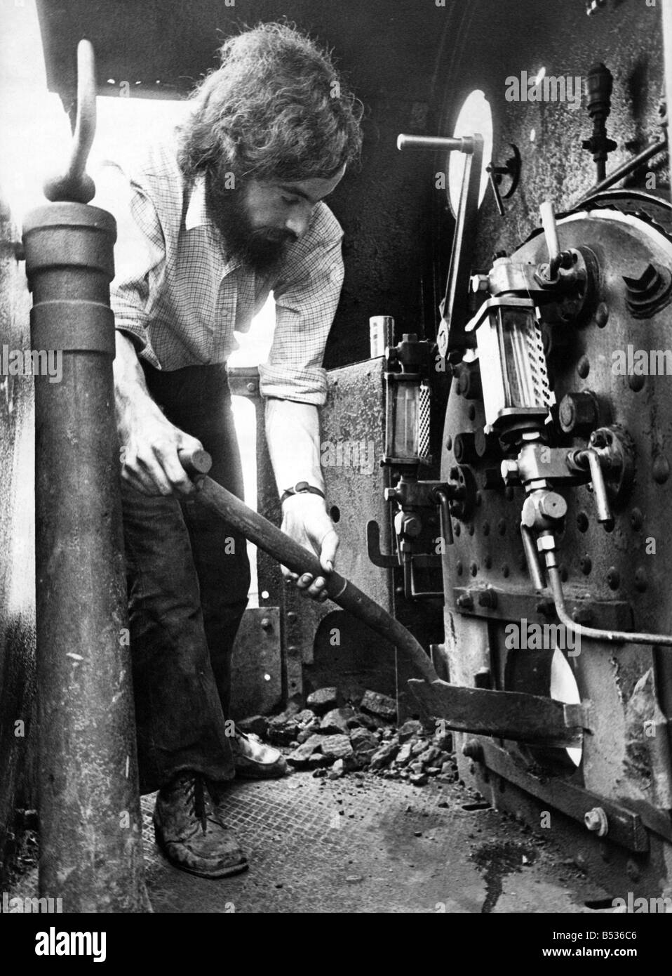 Fuel for the boiler of an old steam engine is shoveled on by Peter Weightman one of the enthusiasts who has helped - Stock Image