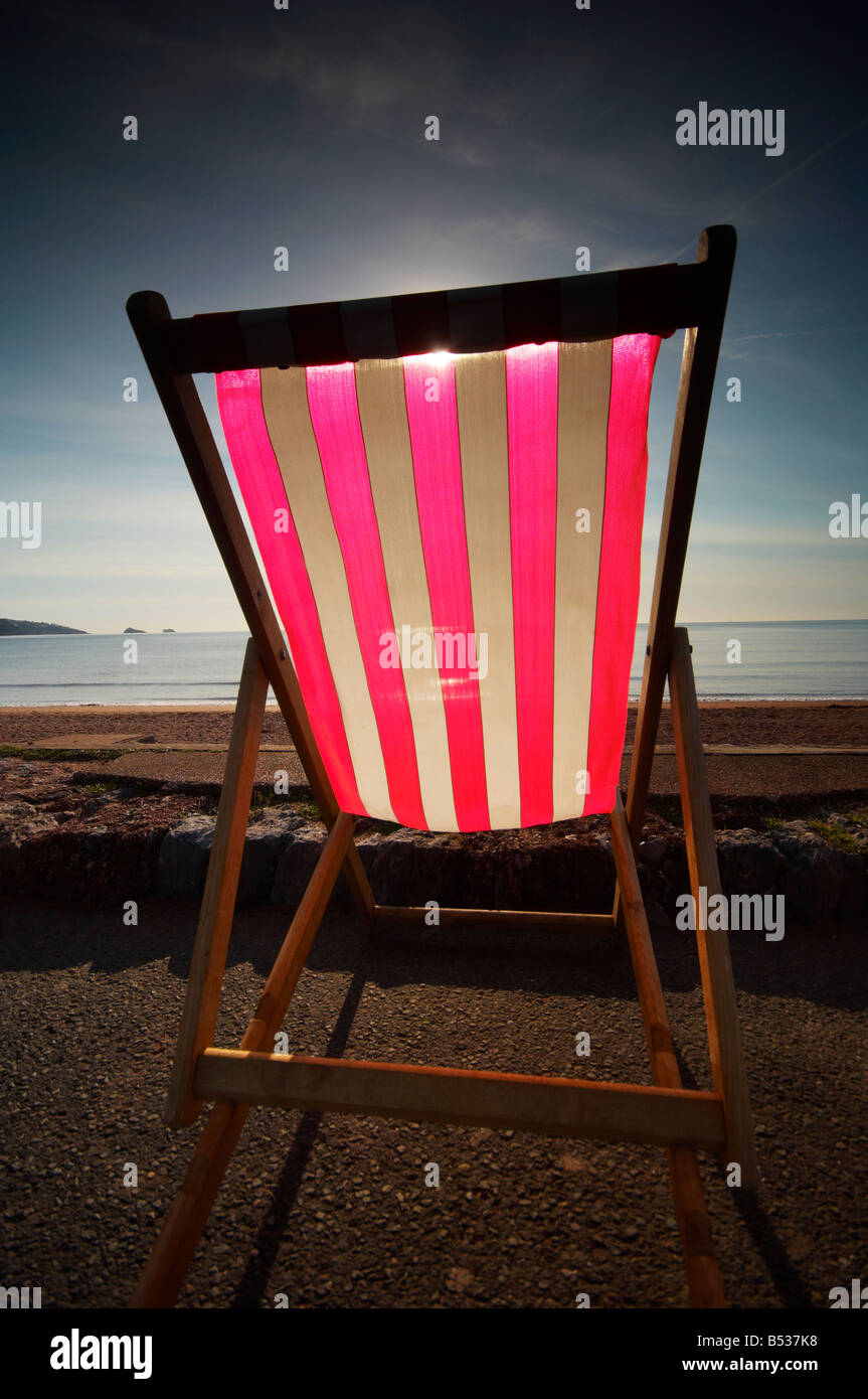 Deckchair backlit by the sun on the English Riviera coast at Paignton Devon UK - Stock Image