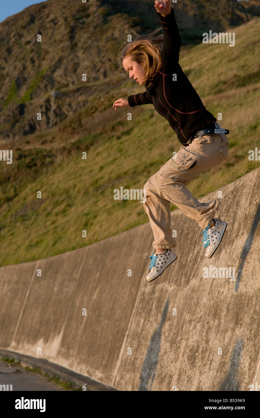 Young Blonde Woman Jumping Off A Wall   Stock Image
