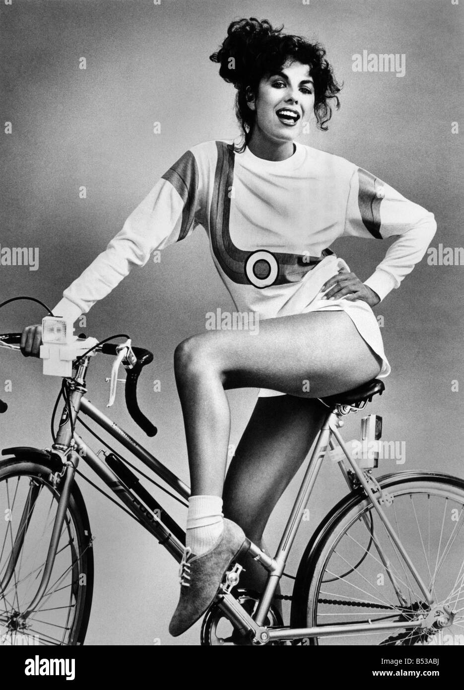 Fashion - Shorts and Hotpants. Short shorts and long sleeved top. Model sits on bicycle. June - Stock Image
