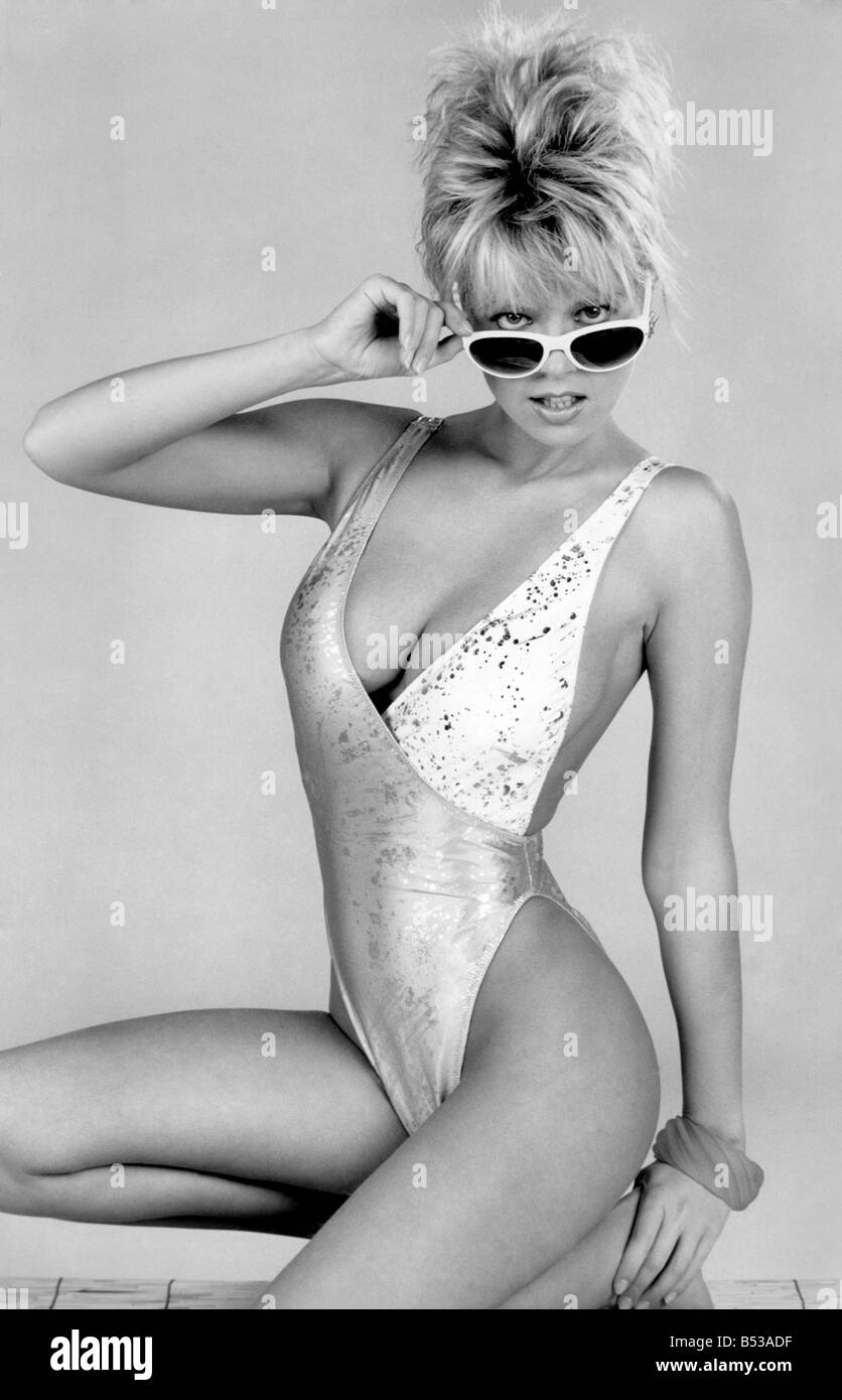 Clothing Beach: Woman models a low cut two-tone swimming costume slashed to stun, and white-rimmed sunglasses. March - Stock Image