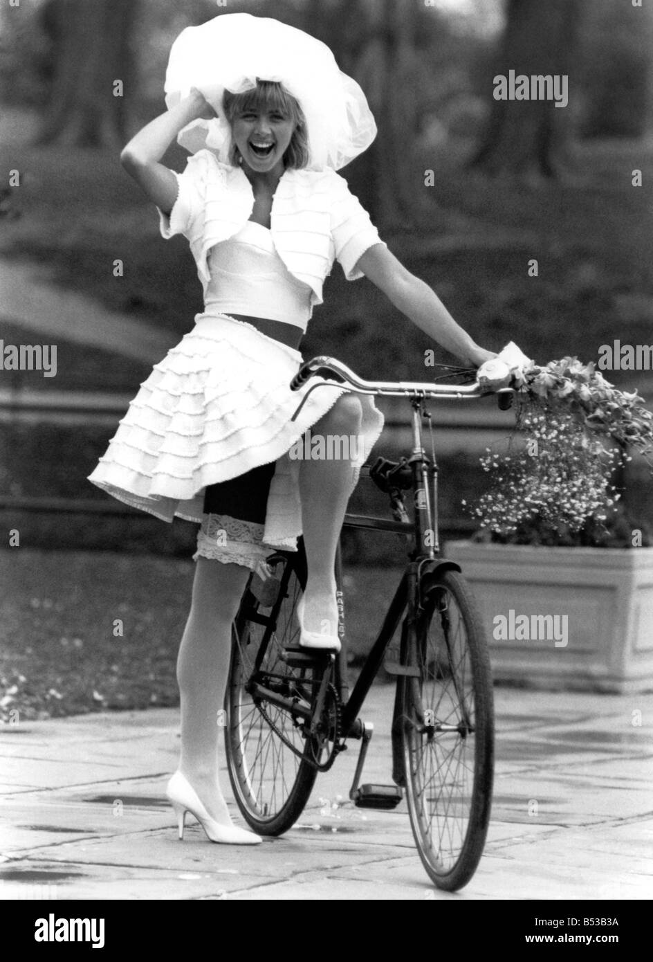 Rubbery Model Jane Sturdy. Wears white outfit, stockings  and frilly hat on bicycle.