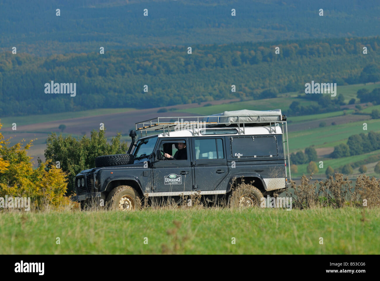 Black 2000s Land Rover Defender 110 on a forest track in the Weserbergland. - Stock Image