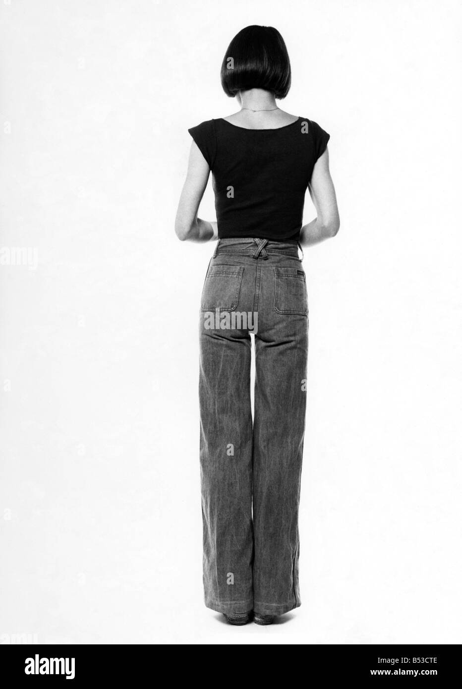 Fashion - 1970s. Back of woman.  Jeans and t-shirt. October 1975 P017333 - Stock Image