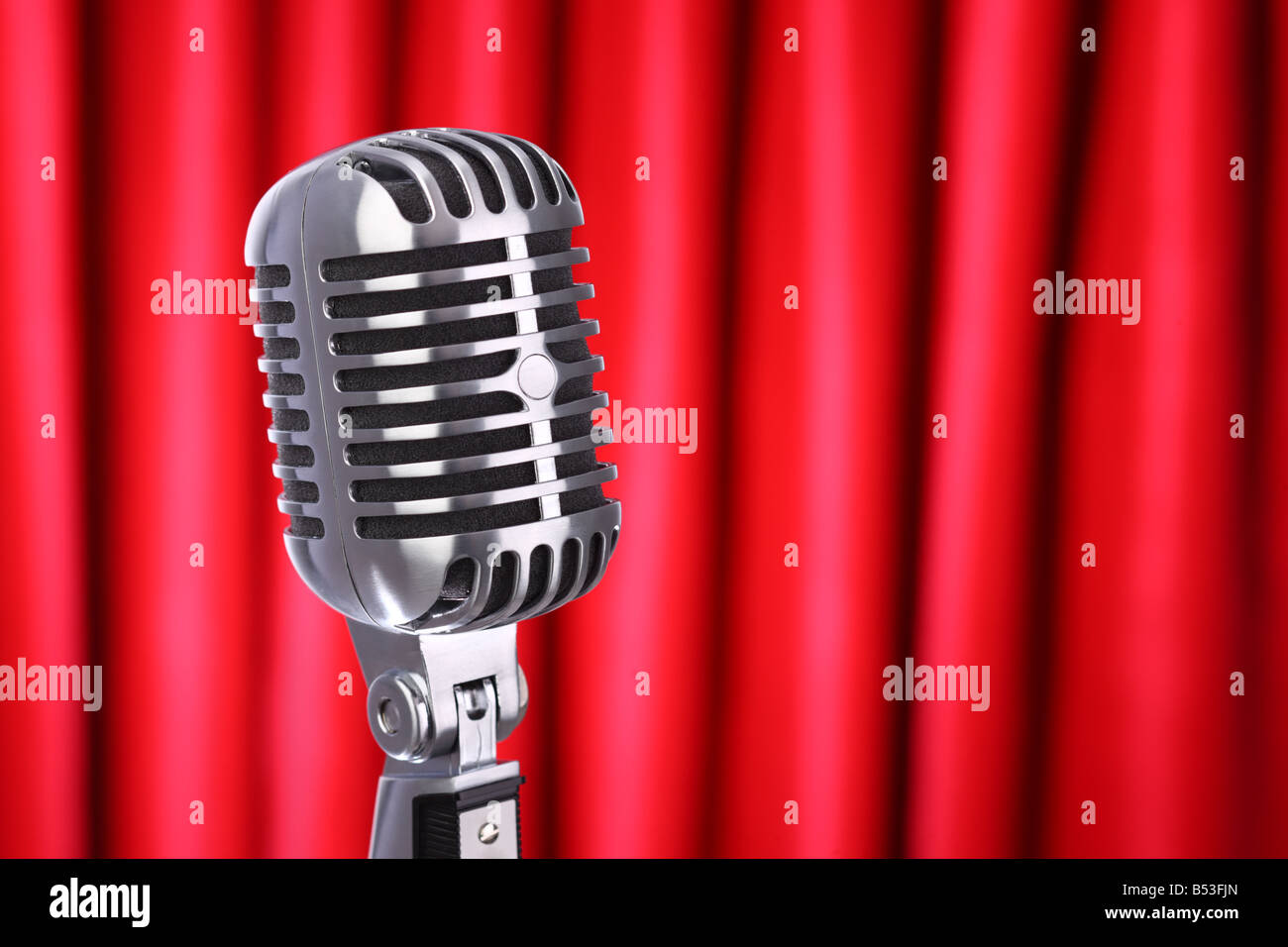 Close up of classic retro microphone with red curtain background - Stock Image