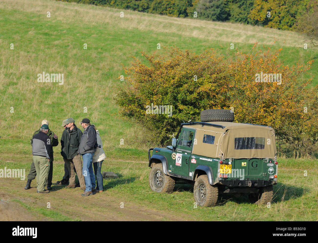 Land Rover crews standing next to a Defender 90 in the hilly Weserbergland. - Stock Image
