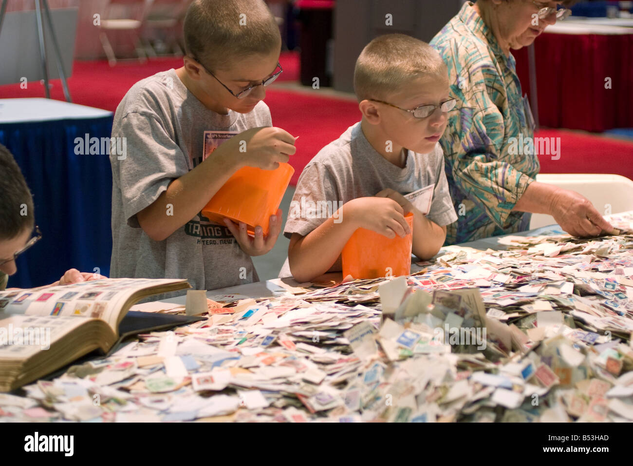 Young stamp collectors intently peruses stamps for sale at a bargain booth at the American Philatelic Society stamp - Stock Image