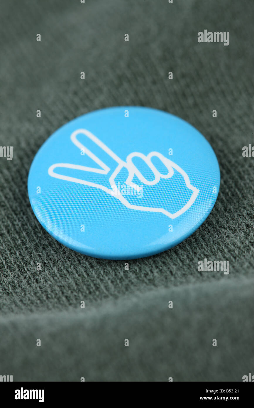 Blue peace pin on shirt - Stock Image