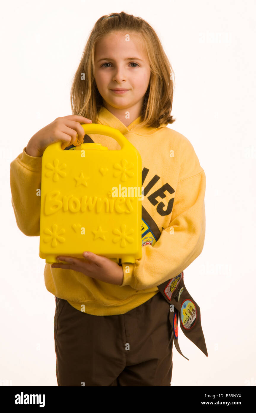 10 year old girl dressed in her Brownies uniform holding her Brownie box - Stock Image