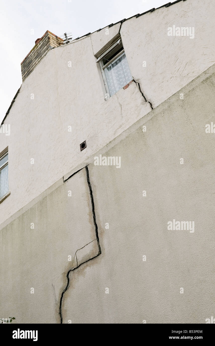 Side of an end of terrace house showing massive crack in the wall caused by subsidence, UK - Stock Image