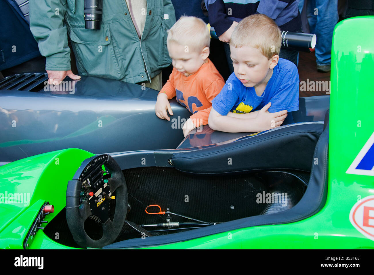 A young car enthusiast studying a Lola car during Lola's 50th Anniversary show in Huntingdon. - Stock Image