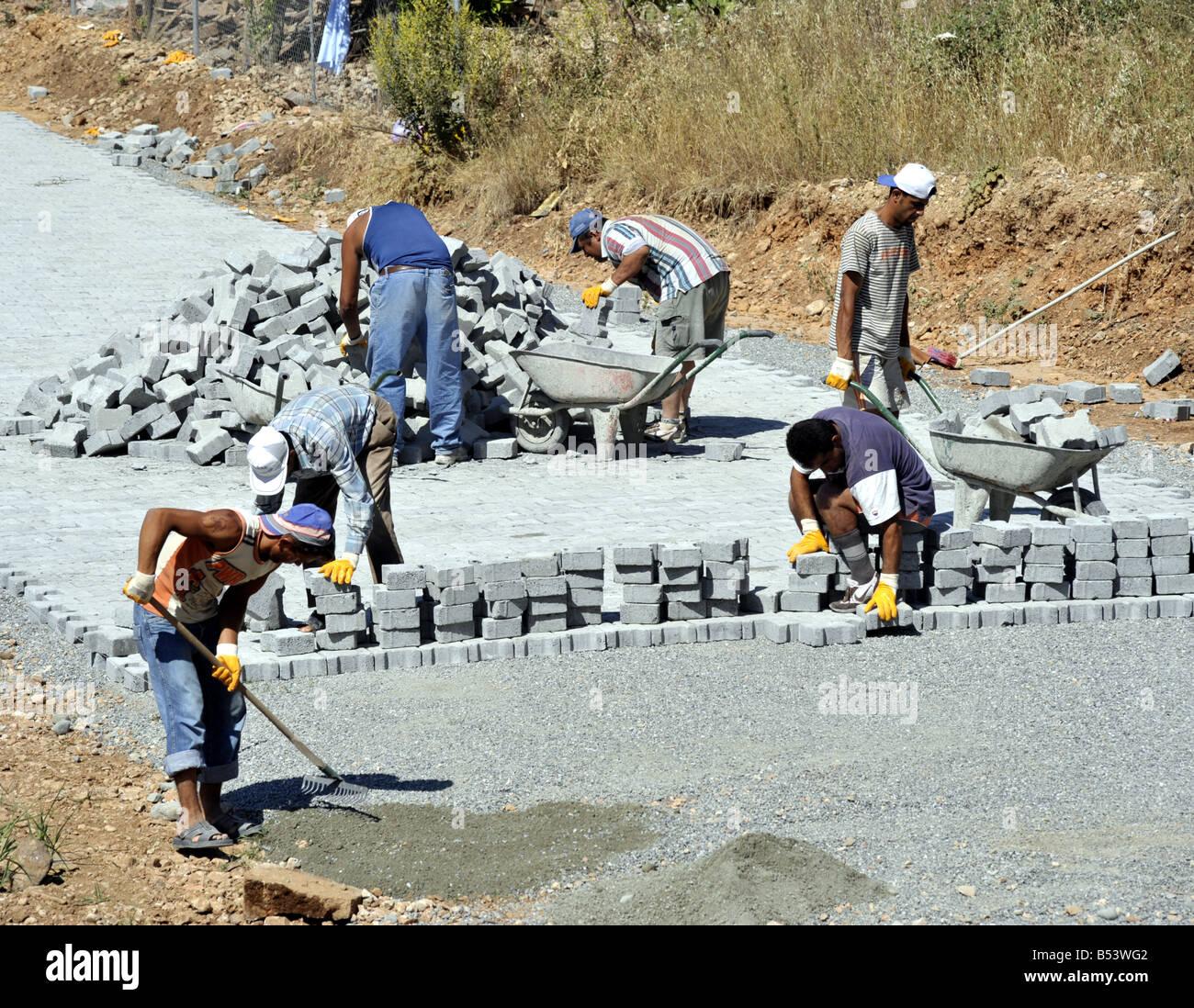 Turkish gang of men bulding block paving road Akyaka Turkey - Stock Image