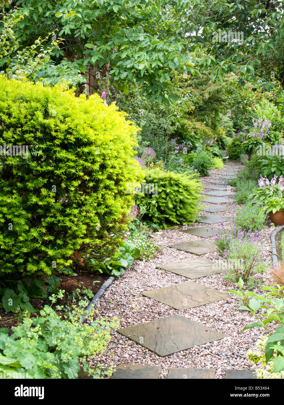 Gravel And Flagged Path Through A Cottage Garden Stock Photo