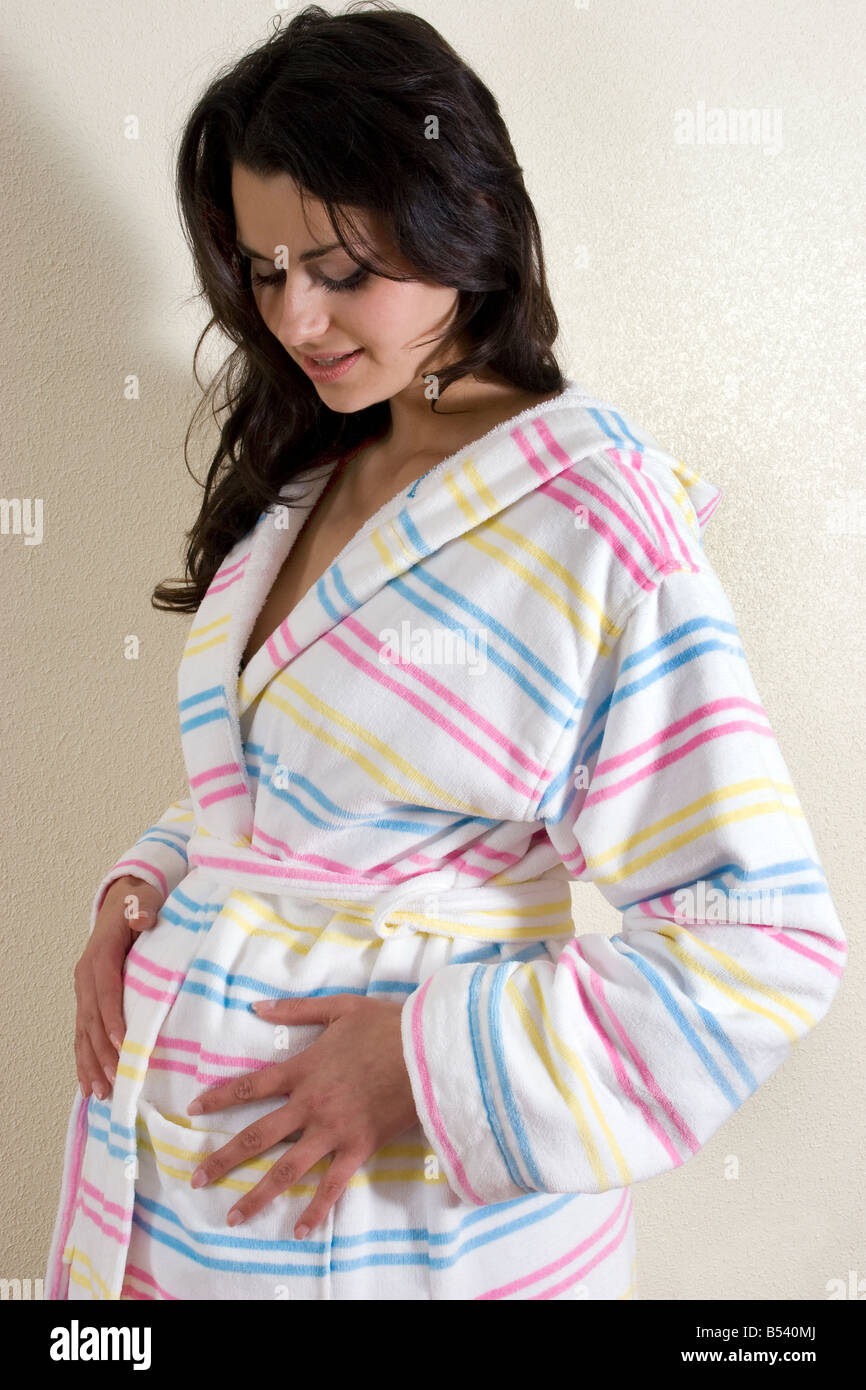 young pregnant woman in dressing gown looking down at her bump Stock ...