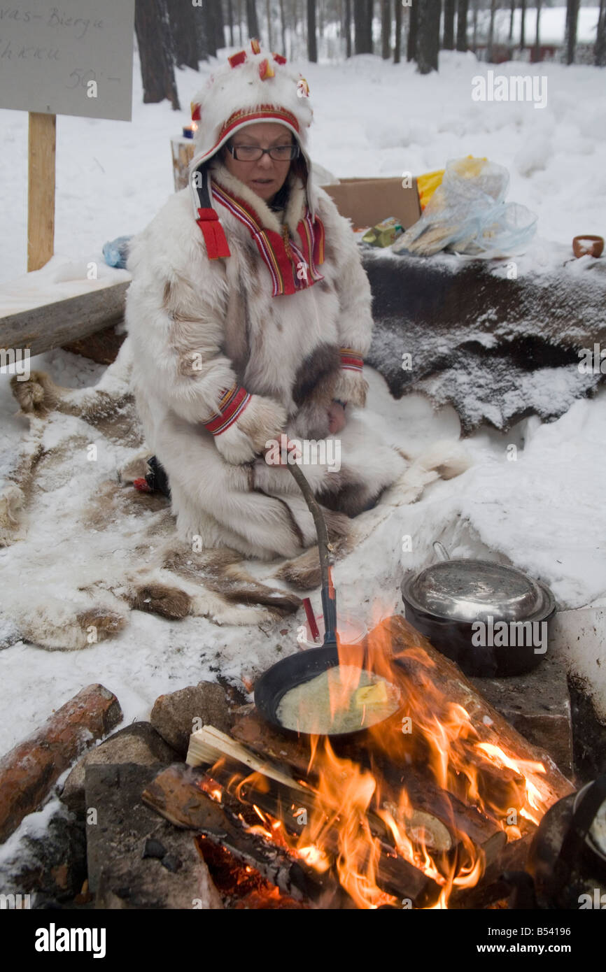 A Same woman coocking on fire Lappland Sweden Winter - Stock Image