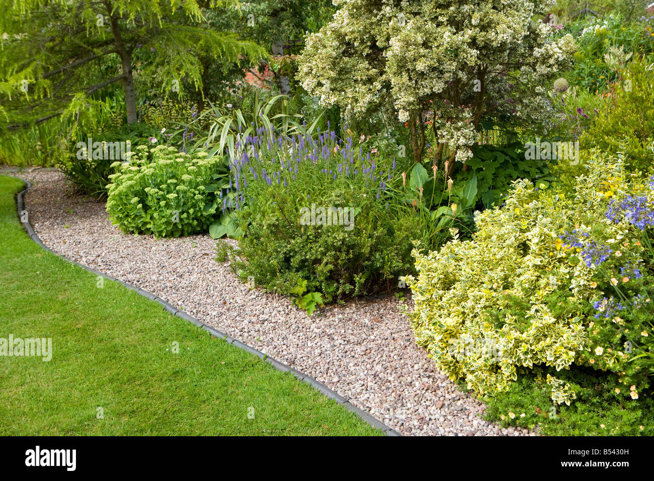 gravel path alongside lawn - Stock Image