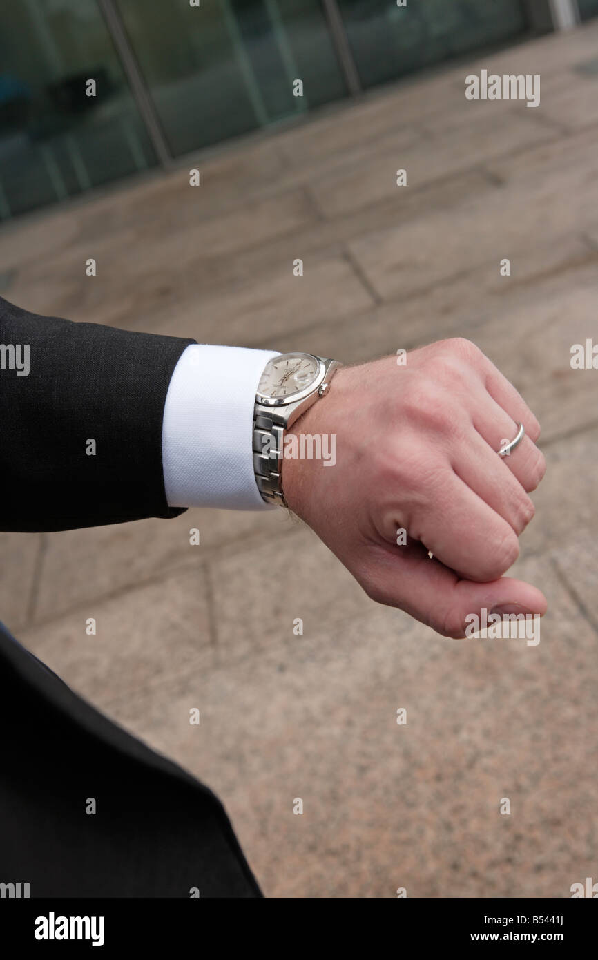 Businessman checking time on watch - Stock Image