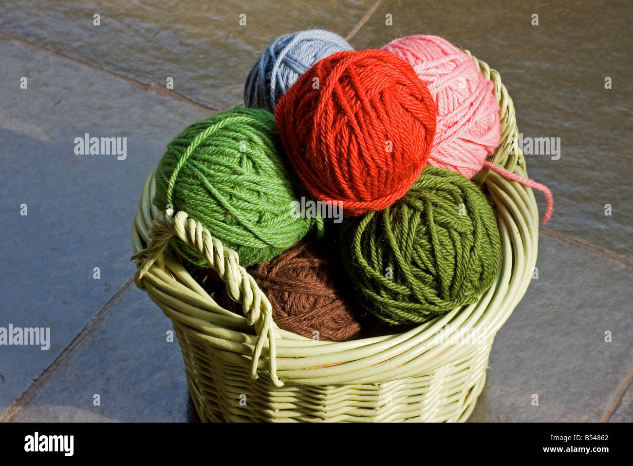 Multicolored skeins of wool in a green basket - Stock Image